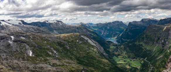 A panorama of the deep blue UNESCO-protected Geirangerfjord and the surrounding majestic, snow-covered mountain peaks, wild waterfalls and lush, green vegetation, Geiranger, Norway; phot