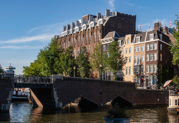 Across the Amstel River on the far left, the A_DAM tower offers a contrast to the older buildings along a canal in Amsterdam, The Netherlands
