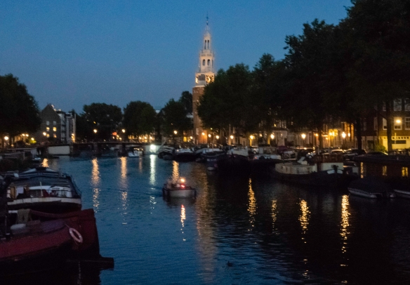 An Amsterdam canal at sunset, with De Oude Kerk (The Old Church), consecrated in 1306, visible in the distance