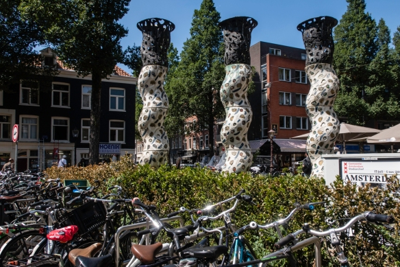 Bicycles are ubiquitous in Amsterdam, The Netherlands, parked here near a statue outside the country_s most famous market, Albert Cuypmarket