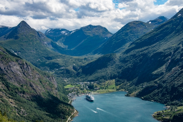 From the Eagle Road viewpoint overlooking Geirangerfjord, the small village of Geiranger, Norway, and the snow-covered, rugged mountains fill the vista