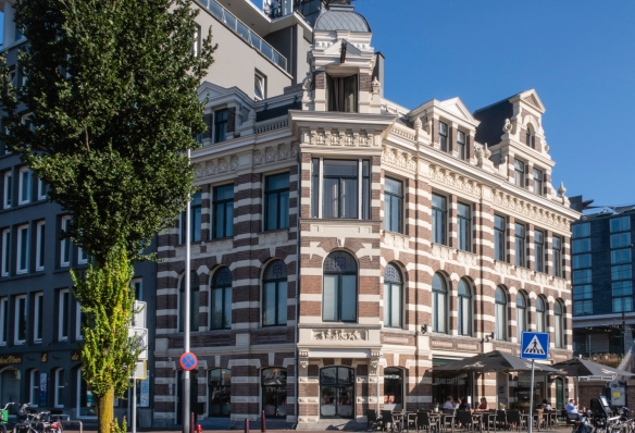 One of the few remaining (restored) historic buildings fronting on the Amstel River, to the east of Amsterdam Centraal (the Amsterdam central train station), in Amsterdam, The Netherland