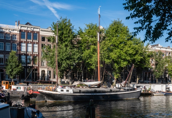 The canals in Amsterdam, The Netherlands, are home to a large variety of boats and watercraft – here a rather large sailboat is berthed next to a private home