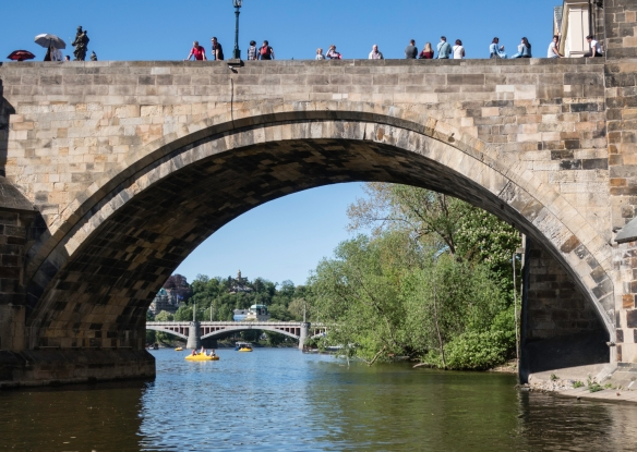 This idyllic scene – having just sailed south under the Charles Bridge on the Vltava River in the center of Prague, Czech Republic, gives a very different vibe than walking through the