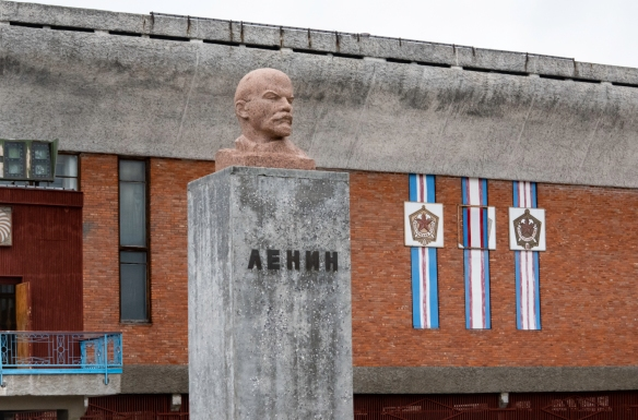 A statue of Lenin and Russian insignia in front of the town_s cultural center, Pyramiden, Spitsbergen Island, Svalbard; [Vladimir Ilyich Ulyanov, better known by the alias Lenin, is re