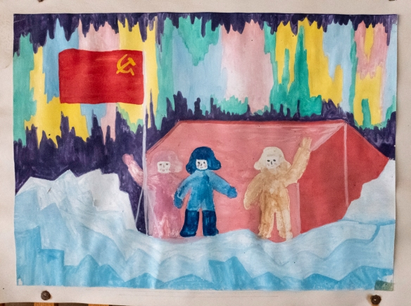 Still hanging on the pegboard on the mezzanine above the lobby of the town_s cultural center is this child_s drawing of 2 children in Pyramiden and the ghost of a comrade child, Pyra