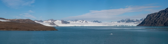 Viewed from our ship at anchor in Signehamna, Krossfjorden, Spitsbergen, Svalbard, the tidewater glacier can be seen to be flowing downhill into the fjord (panorama)