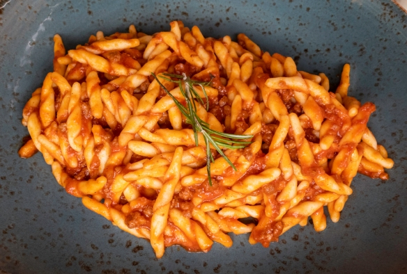 A local Tuscan special pasta, trofie (corkscrew-shaped pasta), in a tomato sauce, luncheon at Osteria del Noce, Marciana Alta, Elba, Italy