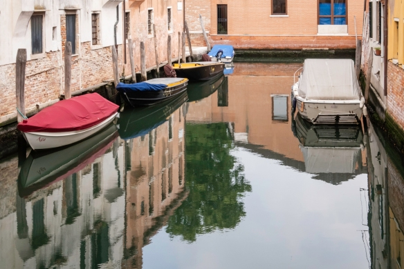 Boats and gondolas are parked all along the canals everywhere in Venice, Italy