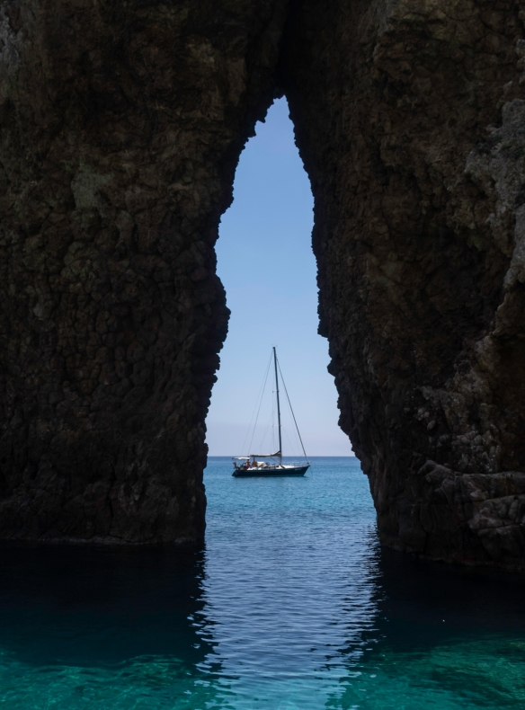 Looking through the natural arch located past the small island of Gavi; Ponza, Italy