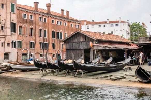 """Near our ship_s pier was this canal with an interesting business located on it – the city_s main gondola repair and painting company, with several gondolas """"dry docked""""; Venice"""
