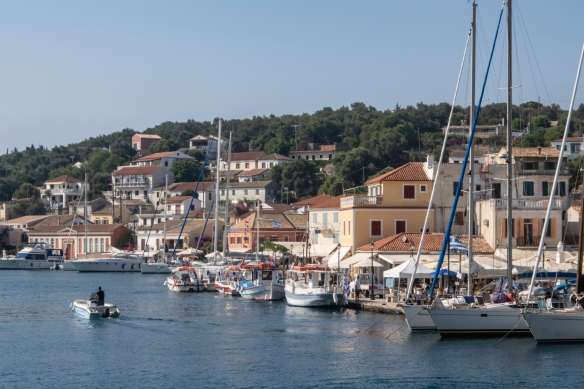 Sleek yachts rest alongside fishing boats and open-air cafés, Gaïos, Paxos Island, Greece