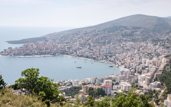 The city of Sarandë is a resort on the Albanian Riviera, in southern Albania, sandwiched between the Ionian Sea and hills of olive groves; the town is on a horseshoe-shaped bay, edged