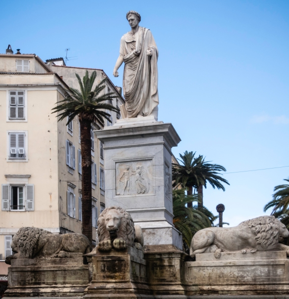 The white marble statue of Napoléon dressed as a Roman Consul, surrounded by four lions and a fountain, is a focal point of the centrally located square, Place Foch, Ajaccio, Corsica (