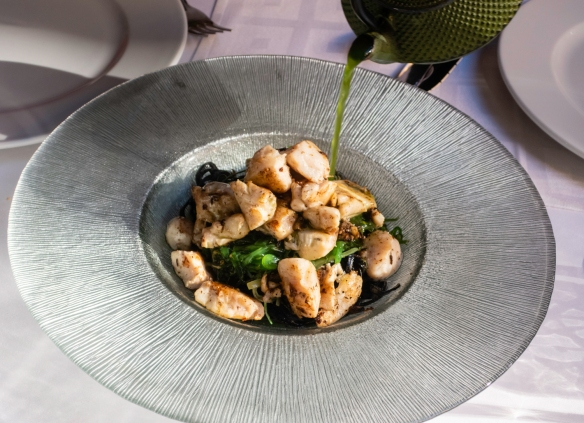 A main course of smoked wreckfish on a bed of black (squid ink) noodles and slivered leeks with the sauce being poured on after the dome lid was removed releasing the smoke; Restaurante