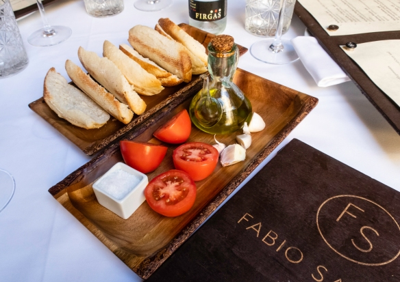 "While we were perusing the menus, we were served the fixings for ""bruschetta"" – the garlic was rubbed onto the toasted bread, then some olive oil was poured on, then slices of toma"