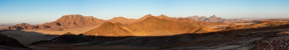 A panorama of some petrified dunes in front of the mountains in NamibRand Nature Reserve, near Sossusvlei, Namibia