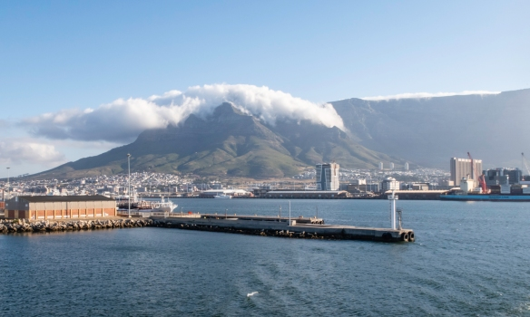 """Almost daily in the summer, the South-East winds blow enough moisture up and over Table Mountain to spread out the """"table cloth"""" on top of the mountain_s plateau, Cape Town, South"""