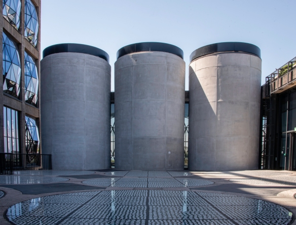 The upper sections of three old concrete grain silos visible across the patio of the rooftop sculpture garden at Zeitz Museum of Contemporary Art Africa, Cape Town, South Africa