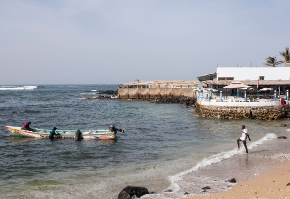 Local fishermen in the water and on their boat in front of a restaurant at the westernmost tip of Senegal and the African continent, Dakar, Senegal