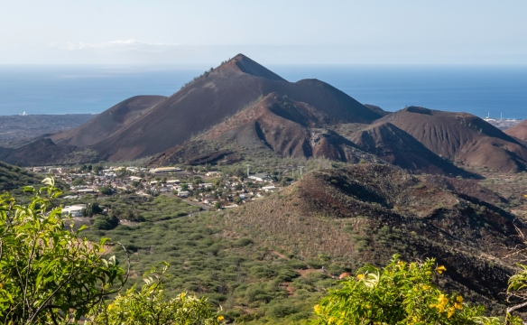 Tucked behind some of Ascension Island_s volcano cones, visible from Green Mountain, is one of several residential neighborhoods that are separate from the main town and capital, Georg