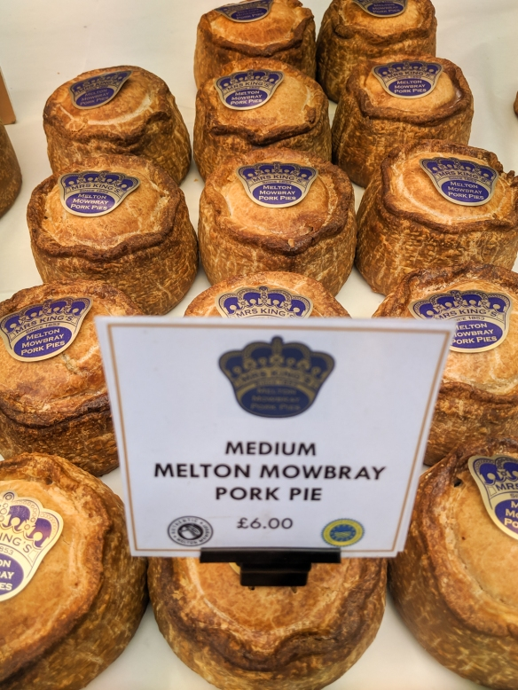 A vendor with a variety of meat pies – featured here are the Melton Mowbray pork pies -- in Borough Market, London, England