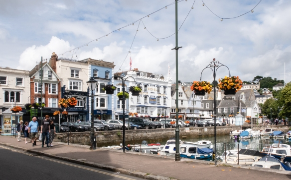 "Picturesque shops lined the street across from the ""Boatfloat"" marina which goes dry when the strong River Dart tide recedes (see photograph, below), Dartmouth, England"