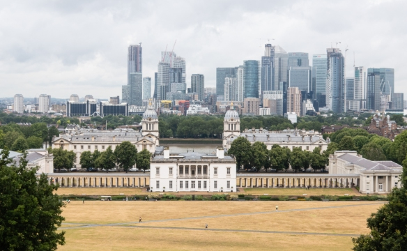 The Old Royal Naval College, with the skyline of London behind it, viewed from the Royal Observatory on a hill in Greenwich Royal Park, Greenwich, London, England
