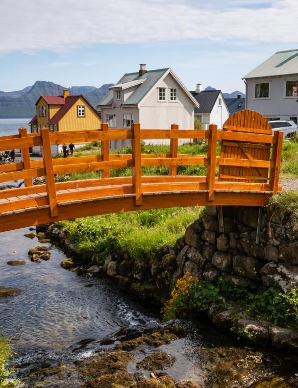 A bridge over a stream by homes overlooking the coastline in Gjógv, Eysturoy, Faroe Islands