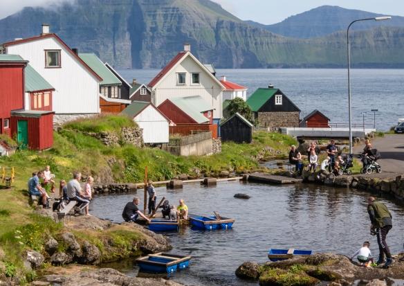 Families enjoying the local pond on a warm summer Sunday in Gjógv, Eysturoy, Faroe Islands