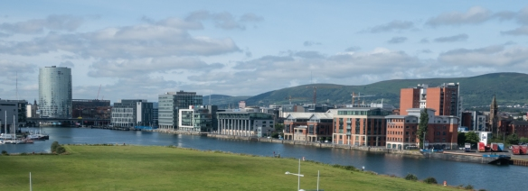 On the left, the tall tower is the Obel Tower, the tallest building in Belfast and Ireland, part of a modernized section of the city's shoreline of the River Lagan, Belfast, Northern Ireland, United Kingdom