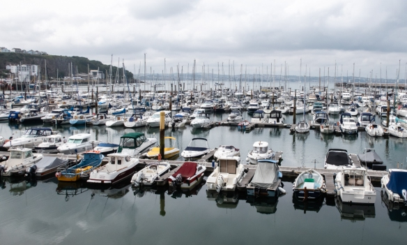 The inner part of Brixham Harbor in Brixham, South Devon, England, is full of working fishing boats; further out, pictured here, are the numerous local and visiting pleasure boats – in the background, just to the east, is the resort town of Torquay