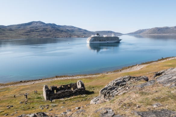The ruins of Hvalsey Church, the largest and one of the best-preserved ruins from the Norse Vikingh period, with our ship anchored in the bay at Thjodhildarstadir, Greenland