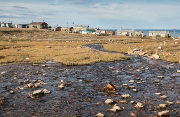 A view of some of the homes in Pond Inlet looking downhill from the new Community Center towards Navy Board Inlet (with Bylot Island across the water), Baffin Island, Nunavut, Canada