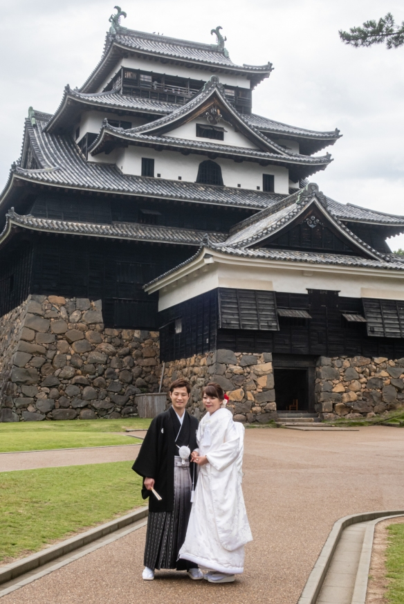 A wedding couple was having their professional wedding photographs made in front of Matsue Castle, Matsue City, Shimane Prefecture on Honshu Island, Japan