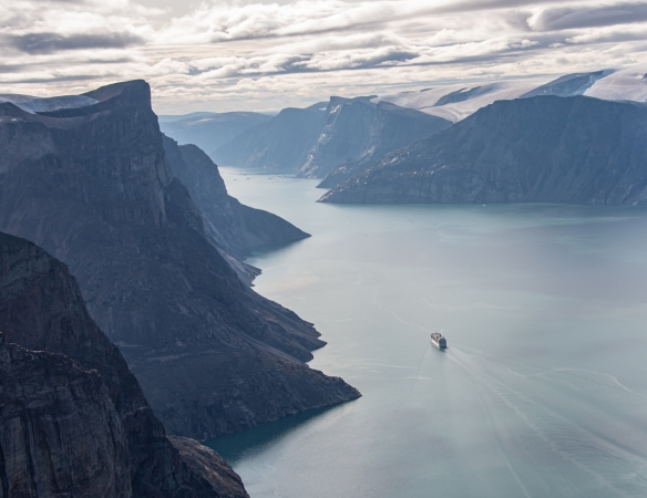Aerial photo of Feacham Bay, Buchan Gulf, Baffin Island, Nunavut, Canada, #1 – our ship in the fjord as seen a few minutes after lifting off from Deck 7 for our scenic helicopter flight and landing on the top of one of the 5,500 feet high cliffs