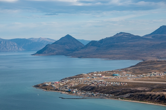 Aerial photo, Pond Inlet, Baffin Island, Nunavut, Canada, #1 – the town of Pond Inlet is in the foreground, with Bylot Island with the mountain glaciers in the distance, across Navy Board Inlet