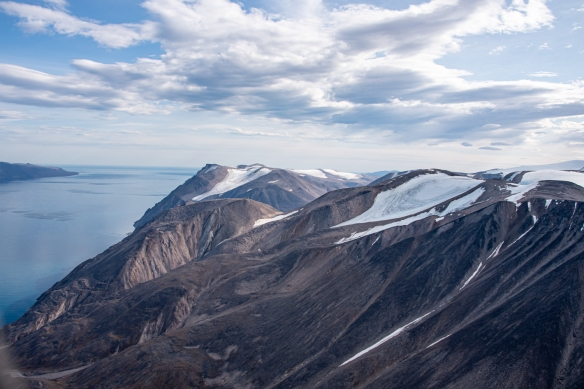 Aerial photo, Pond Inlet, Baffin Island, Nunavut, Canada, #4 – the transition is quite stark at the top of the cliffs from the barren soil and verticality of the cliffs fronting the waterfront to the numerous glaciers on the top of Baffin Island