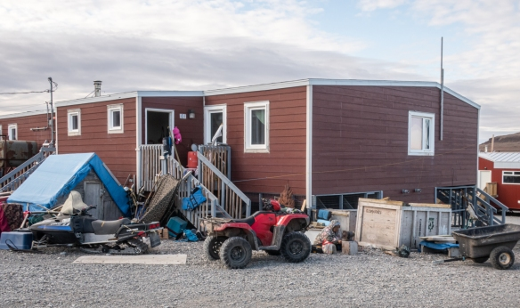 Another typical home in Ulukhaktok; note the two critical vehicles in the front yard – a quad bike for the summer and a skidoo for the winter; Victoria Island, Northwest Territories, Canada