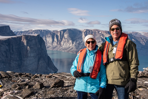 Cliff top photo of Feacham Bay, Buchan Gulf, Baffin Island, Nunavut, Canada, #2 – the intrepid explorer and your blogger at an elevation of 5,500 feet overlooking the spectacular fjord after disembarking from our helicopter on the cliff top