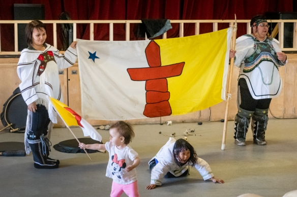 Local Inuit women and children who performed in the cultural performances at the Pond Inlet Community Center for us – shown holding the flag of the Nunavut Territory, Canada
