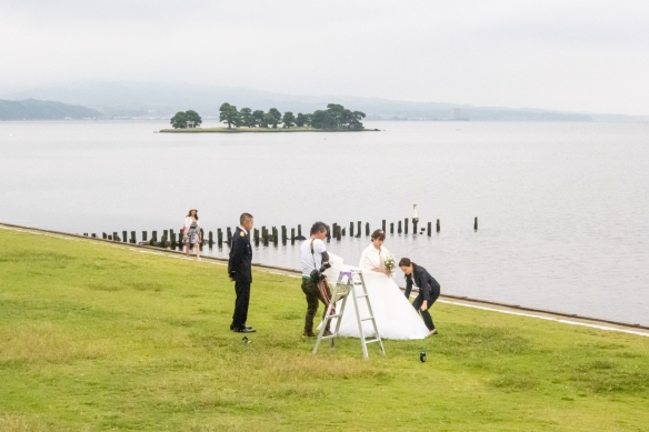 Shimane Art Museum #9, Matuse, Shimane Prefecture, Honshu Island, Japan – a wedding couple is preparing for a photography session on the shore of Lake Shinji by the museum