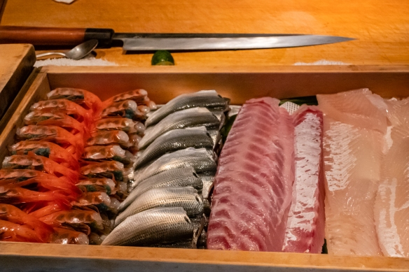 The chef's sushi knife and a selection of fresh fish and prawns in the cooler at the preparation counter, viewed from our seats; Otomezushi, Kanazawa, Honshu Island, Japan