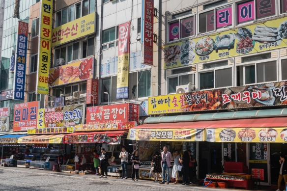 A street full of fish and seafood stores and restaurants, across from the Jagalchi Seafood Market in downtown Busan, South Korea