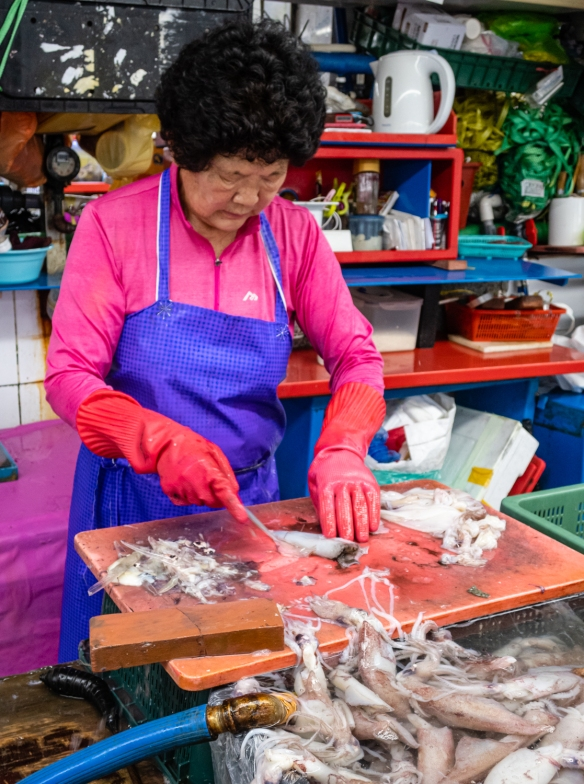 A vendor – a Jagalchi Ajumma (married woman) – cleaning squid at her stall in Jagalchi Seafood Market, Busan, South Korea