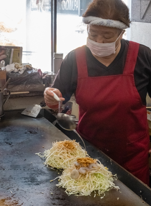 After making the pancakes on the griddle, the okonomiyaki were piled high with shredded cabbage, proteins (pork in one, pork and shrimp in a second), with oil for cooking poured on; Okonomimura, Hiroshima, Honshu Island, Japan