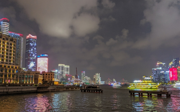 In the center, brightly lighted river boars sail by while our ship is docked behind the red crane (center left) at the Shanghai Port International Cruise Terminal, just a short walk from the Hyatt on the Bund Hotel