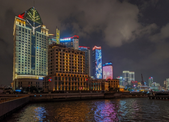 Newer tall and brightly lighted buildings on the west side of the Huangpu River photographed from Huangpu Park just south of Waibaidu Bridge and the Shanghai Port International Cruise Terminal, Shanghai, China