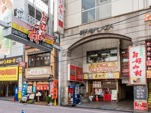 "Okonomimura (on the right), an 8-story building with a collection of okonomiyaki restaurants on the second, third and fourth floors, all little mom-and-pop, hole-in-the-wall ""restaurants"" specializing in the city's signature meal, okonomiyaki"