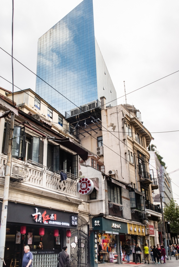 Quite a contrast between the 100-year old two-story buildings on the north side of Nanjing Road Pedestrian Street and the 21st century skyscraper on the south side, Shanghai, China